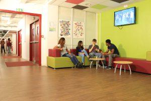 4 étudiants assis sur un canapé dans une salle discutent en prenant une collation