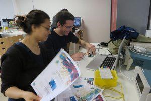 2 étudiants à leur bureau manipulent des feuilles de cours et un circuit imprimé